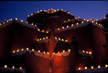 This undated image provided by New Mexico Tourism shows farolitos, which are candles in paper bags, flickering against the night sky atop Santa Fe's Inn at Loretto. The farolito lanterns, also called luminarias, are a New Mexico holiday tradition.