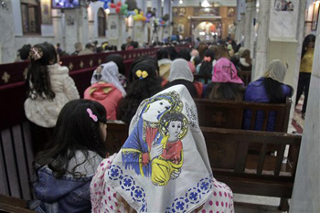 Worshippers attend Orthodox Christmas Eve Mass, where an Oct. 2013 deadly drive-by-shooting killed several at a wedding party, in the Warraq neighborhood of Cairo, Egypt late Monday, Jan. 6, 2014.