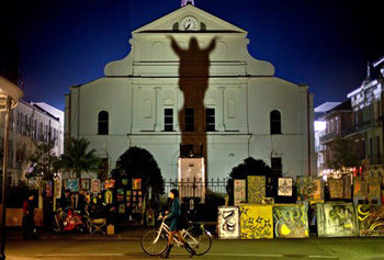 "In this Friday, Feb. 1, 2013 file photo, a pedestrian walks her bicycle past a silhouette of Jesus Christ projected against the Cathedral-Basilica of Saint Louis King of France in New Orleans, two days ahead of the NFL Super Bowl football game between the San Francisco 49ers and the Baltimore Ravens. ""I find it fascinating that that's what people really want to know -- what race was Jesus."