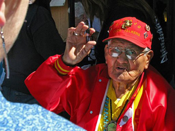 "This Oct. 3, 2009, file photo, shows Navajo Code Talker Chester Nez speaking to a woman outside an Albuquerque, N.M., tourist shop during a book signing event for ""Navajo Weapon."" Nez, the last of the 29 Navajos who developed an unbreakable code that helped win World War II, died Wednesday morning, June 4, 2014, of kidney failure at his home in Albuquerque. He was 93."
