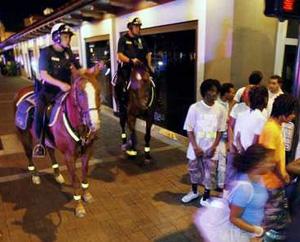 Policemen on horses patroling black teenagers
