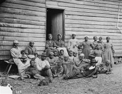former slaves sitting in front of a typical home, date unknown