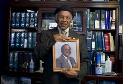 Abdulah Salim, Jr. hold the photograph of his father Dr. Reginald A. Hawkins