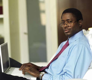 an African-American man typing on a laptop computer