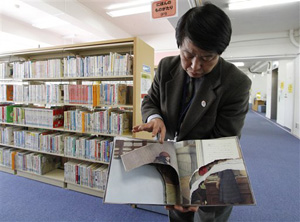 "This ripped copy of Anne Frank's ""Diary of a Young Girl"" picture book is shown by Shinjuku City Library Director Kotaro Fujimaki at the library in Tokyo Friday, Feb. 21, 2014. A total of 265 books in 31 libraries had been found damaged after the first damaged book was found in January, prompting a wider search."