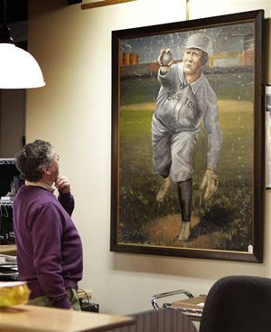 In this photo made Tuesday, March 11, 2014, auctioneer Floyd Hartford examines a 1910 painting of Cy Young in a Boston Red Sox uniform at the Saco River Auction House in Biddeford, Maine.