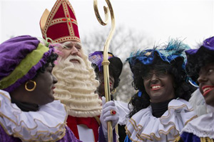 "In this Nov. 16, 2013 file photo the Dutch version of Santa Claus, Sinterklaas, or Saint Nicholas, and his sidekicks known as ""Zwarte Piet"" or ""Black Pete"" arrive by steamboat in Hoorn, north-western Netherlands. A large majority of the Netherlands' mostly-white population say Pete is a positive figure and deny any racial insult. But a court and racism experts have found his appearance offensive."