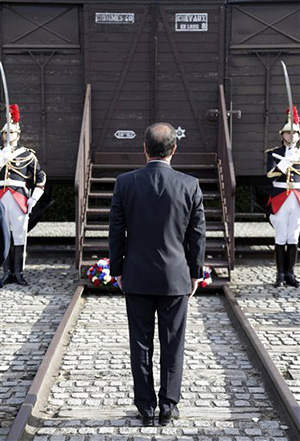 This Sept. 21, 2012, file photo shows French President Francois Hollande standing at attention in front of a train car symbolizing the Drancy camp during the inauguration of the new Shoah memorial in Drancy, a Paris suburb, France. Hundreds of Americans and others deported by France's state rail company SNCF during the Nazi occupation will be entitled to compensation from a $60 million compensation fund that will be financed by France and managed by the United States.