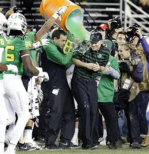 Oregon coach Mark Helfrich is drenched with a green liquid during the second half of a Pac-12 Conference championship against Arizona NCAA college football game Friday, Dec. 5, 2014, in Santa Clara, Calif. Oregon won, 51-13.