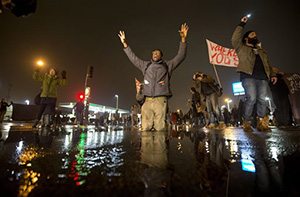 Anthony Grimes kneels on a rain-soaked street as he blocks traffic with other protesters Sunday, Nov. 23, 2014, in St. Louis. Ferguson and the St. Louis region are on edge in anticipation of the announcement by a grand jury whether to criminally charge officer, Darren Wilson in the killing of 18-year-old Michael Brown.