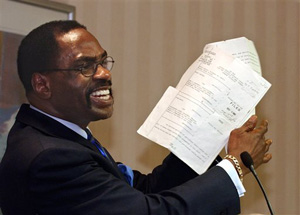 "In this Jan. 29, 2004 file photo, former boxer, Rubin, ""Hurricane"" Carter, holds up the writ of habeas corpus that freed him from prison, during a news conference held in Sacramento, Calif."