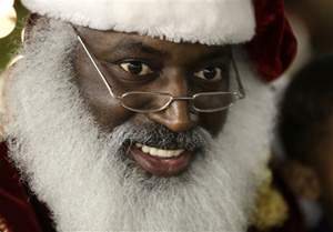 "In this Tuesday, Dec. 17, 2013 photo, Dee Sinclair, portraying Santa Claus, reads a story to children in Atlanta. ""Kids don't see color. They see a fat guy in a red suit giving toys,"" says Sinclair, 50."