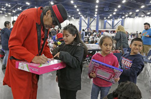 "Pancho Claus, portrayed by Richard Reyes, autographs gifts at a charity holiday event Saturday, Dec. 14, 2013, in Houston. ""For these diverse times, it's important for children to see Santa in all these different forms,"" Reyes said."
