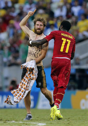 Ghana's Sulley Muntari assists the Neo-Nazi sympathizer off the pitch after he ran on during the group G World Cup soccer match between Germany and Ghana at the Arena Castelao in Fortaleza, Brazil, Saturday, June 21, 2014.