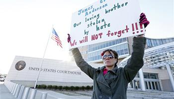Amelie Hahn, braves cold weather as she holds a poster memorializing the 2011 rundown death of James Craig Anderson in front of the federal courthouse in Jackson, Miss., Wednesday, Jan. 7, 2015. Two of the men charged in the series of 2011 racial beatings that resulted in Anderson's death attended change-of-plea hearing.