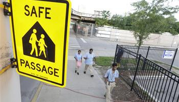 School Children walk a safe passage route along 63rd Street on the opening day of school this week, in Chicago. Chicago children returned to school walking past even more guards than last year, when concerns about safety prompted the city to line the streets with 1,200 adults every day.