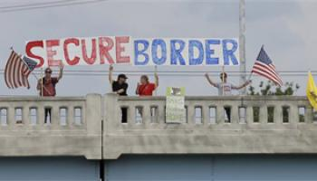 This July 18, 2014, file photo shows demonstrators with signs on an overpass in Indianapolis, to protest against people who immigrate illegally.