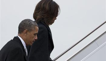President Barack Obama and first lady Michelle Obama board Air Force One to travel to South Africa for a memorial service in honor of Nelson Mandela on Monday, Dec. 9, 2013 in Andrews Air Force Base, Md.