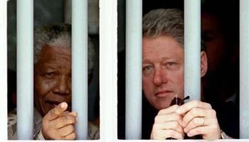 In this March 27, 1998 file photo, South African President Nelson Mandela, left, and U.S. President Bill Clinton peer through the bars of prison cell No. 5, the cramped, gray cell where Mandela was jailed for 18 years in his struggle against apartheid, on Robben Island, South Africa. South Africa's president Jacob Zuma says, Thursday, Dec. 5, 2013, that Mandela has died. He was 95.