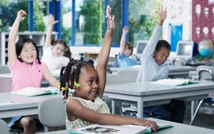 Children in a classroom raising hands to answer the teacher