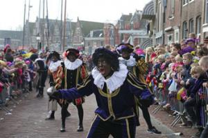 "In this Nov. 16, 2013 file photo a ""Zwarte Piet"" or ""Black Pete"", jokes with children after arriving with Sinterklaas, or Saint Nicholas, by steamboat in Hoorn, north-western Netherlands. Amsterdam's mayor and organizers of a large children's winter festival have unveiled plans on Thursday, Aug. 14, 2014 to reform the image of ""Black Pete"" in order to remove perceived racist elements over a period of years."