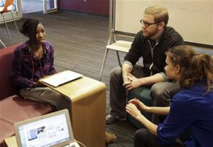 English teacher Tom Rademacher talks with his high school juniors Kierra Murray, left, and Ana Silverman, right, Tuesday, Dec. 2, 2014, at Fair School in Minneapolis. Knowing that the grand jury decision not to indict a white officer who shot and killed a black teen in Ferguson, Mo., would be on the minds of his students, Rademacher put aside his lesson plans and asked them a question: How did they feel?