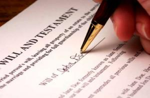 a hand signing a Will document