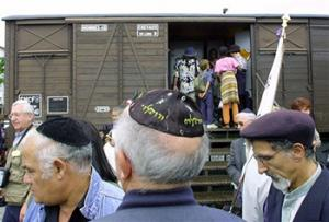 This Aug. 20, 2001, file photo shows French Holocaust survivors gathering at the site of the former Drancy detention camp, north of Paris, France. From Aug. 20, 1941 until the end of World War II, more than 70,000 Jewish men, women and children passed through Drancy on their way to Nazi extermination camps, particularly Auschwitz. The wagon is part of the memorial site.