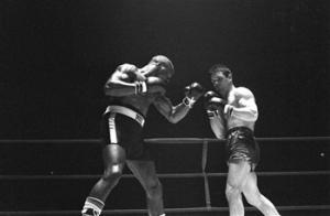 "In this Feb. 23, 1965 file photo, Rubin ""Hurricane"" Carter, left, knocks out Italian boxer Fabio Bettini in the 10th and last round of their fight at the Falais Des Sports in Paris. Carter, who spent almost 20 years in jail after twice being convicted of a triple murder he denied committing, died at his home in Toronto, Sunday, April 20, 2014."