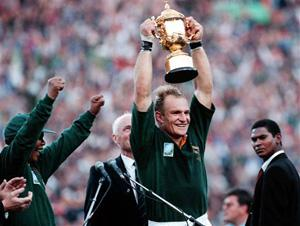 In this June 24, 1995, file photo, South African rugby captain Francios Pienaar, center, raises the trophy after receiving it from South African President Nelson Mandela, left, who wears a South African rugby shirt, after they defeated New Zealand in the final 15-12 at Ellis Park, Johannesburg. Mandela strode onto the field wearing South African colors and bringing the overwhelmingly white crowd of more than 60,000 to its feet.