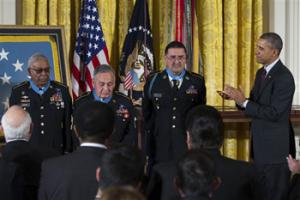 President Barack Obama applauds, from left, Staff Sgt. Melvin Morris, Sgt. 1st Class Jose Rodela, and Spc. Santiago J. Erevia after he awarded them with the Medal of Honor during a ceremony in the East Room of the White House in Washington, Tuesday, March 18, 2014.