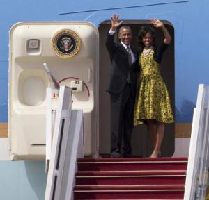 Barack and Michelle Obama waving from the door of Air Force One